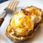 a loaded twice baked potato on a small white plate