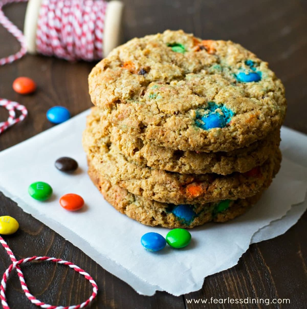 a stack of four large M and M cookies on a napking
