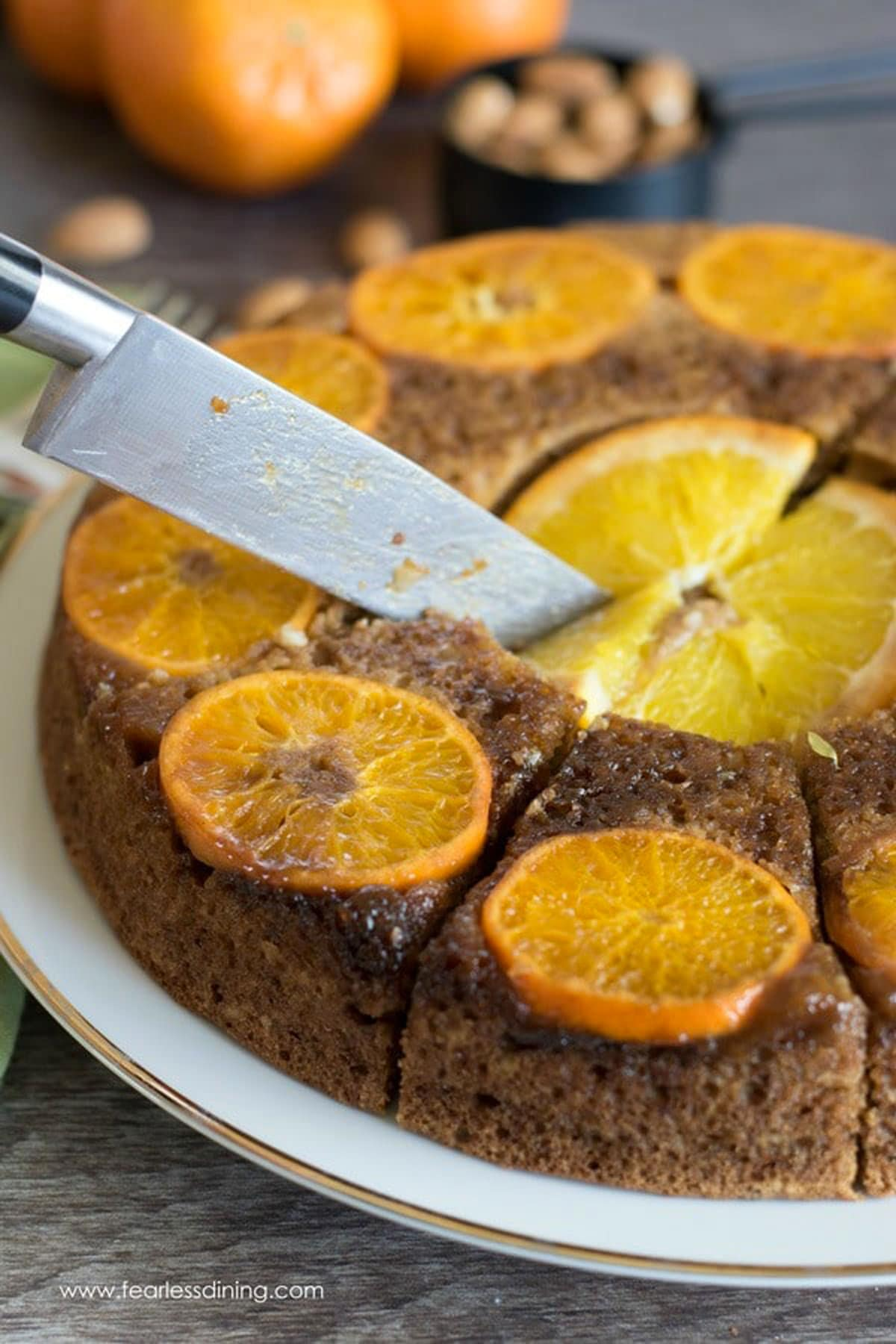 cutting the orange cake with a knife