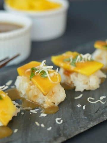 mango dessert sushi on a slate serving platter
