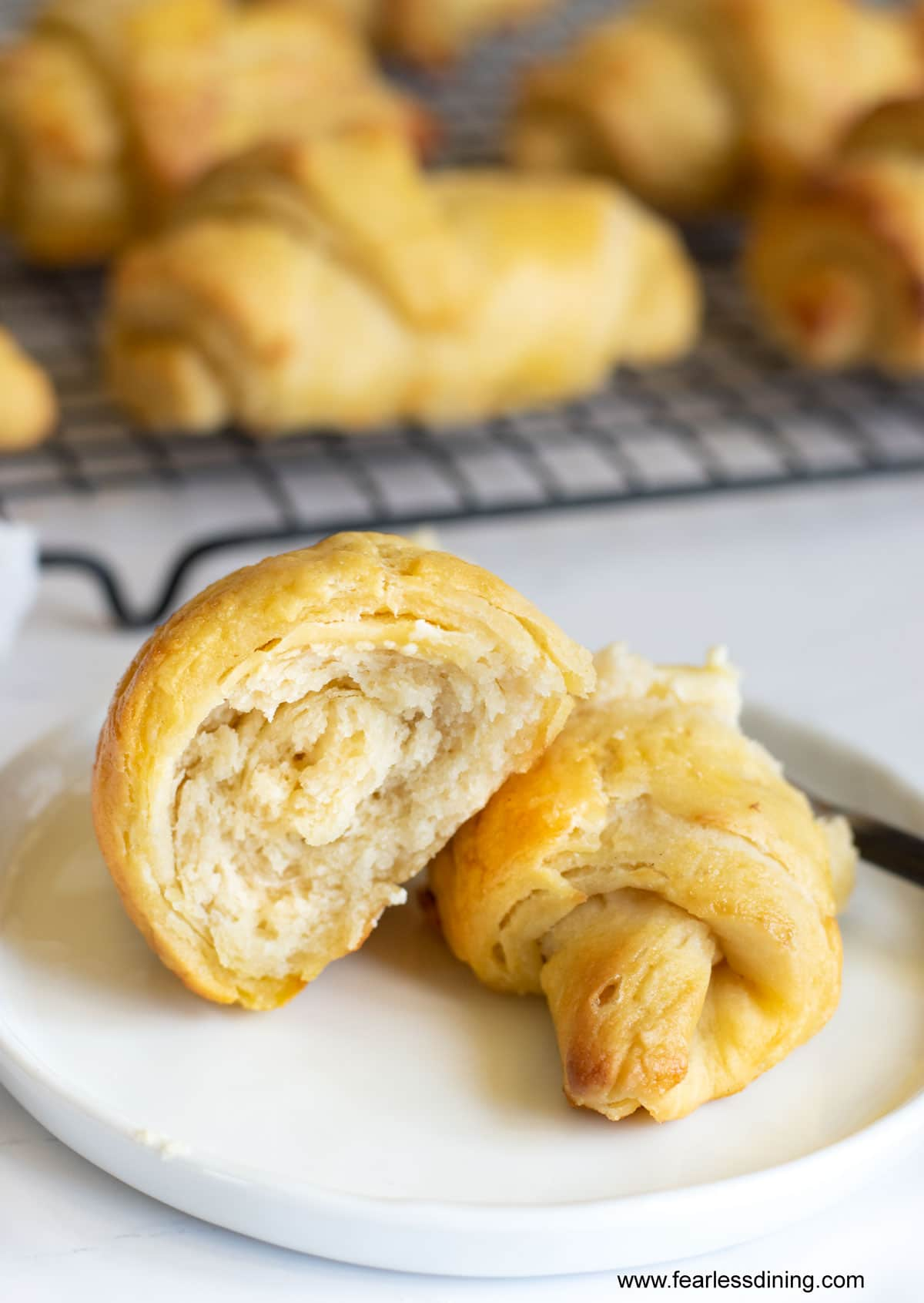 two halves of a crescent roll on a white plate