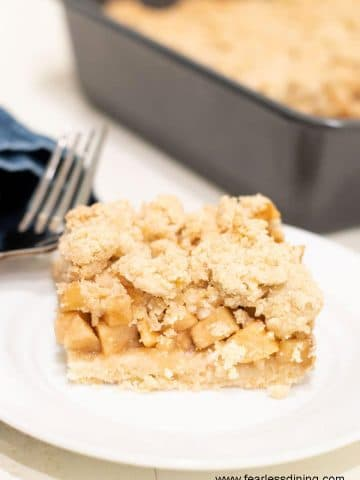 a slice of gluten free apple crumble bar on a small white plate