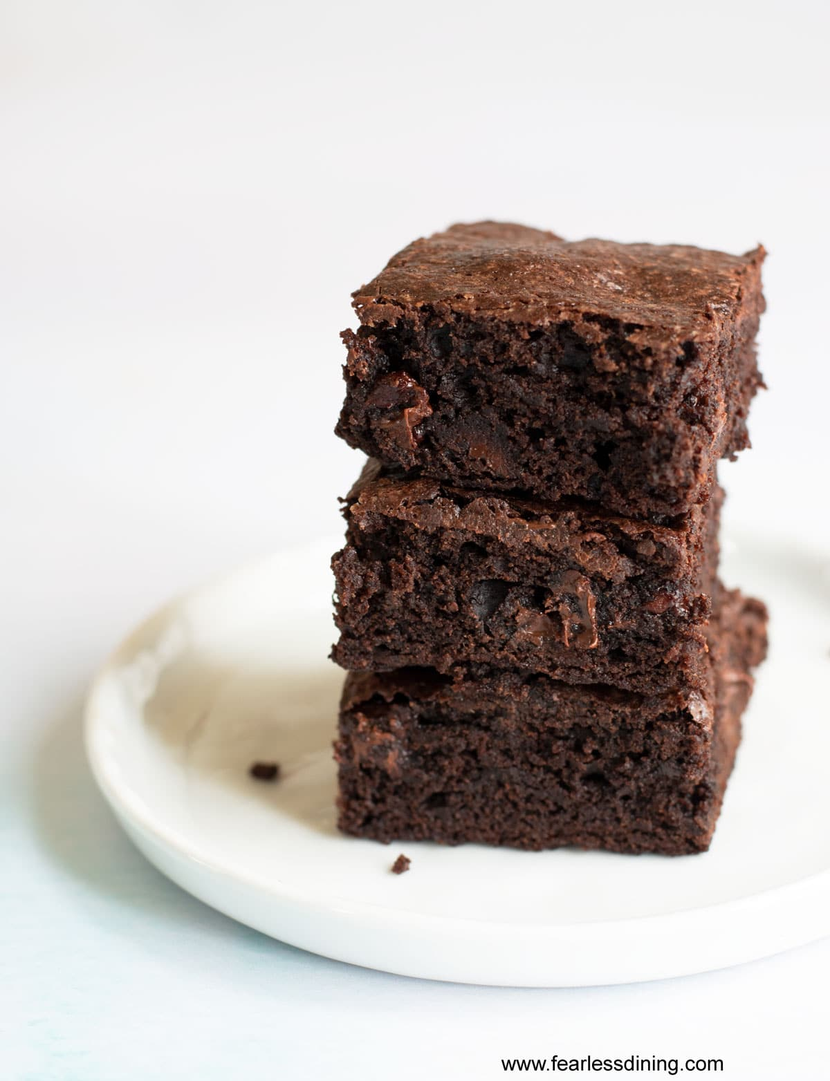 a stack of three fudgy brownies on a white plate