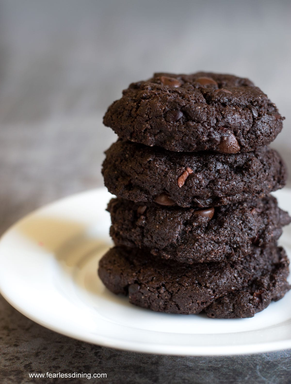 a stack of four chocolate espresso cookies stacked on a plate
