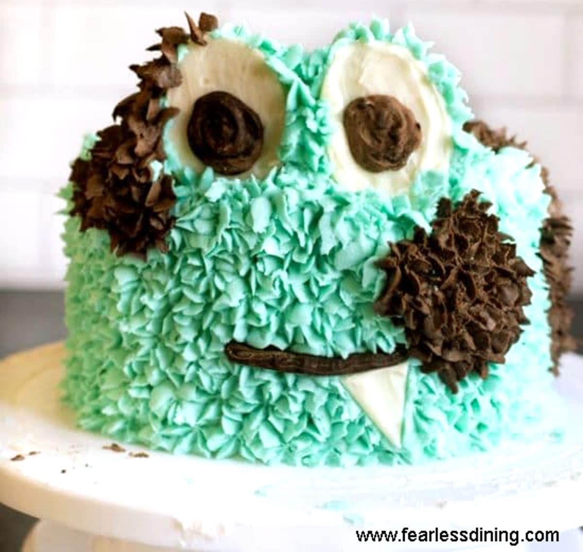 a finished cake decorated like a turquoise monster