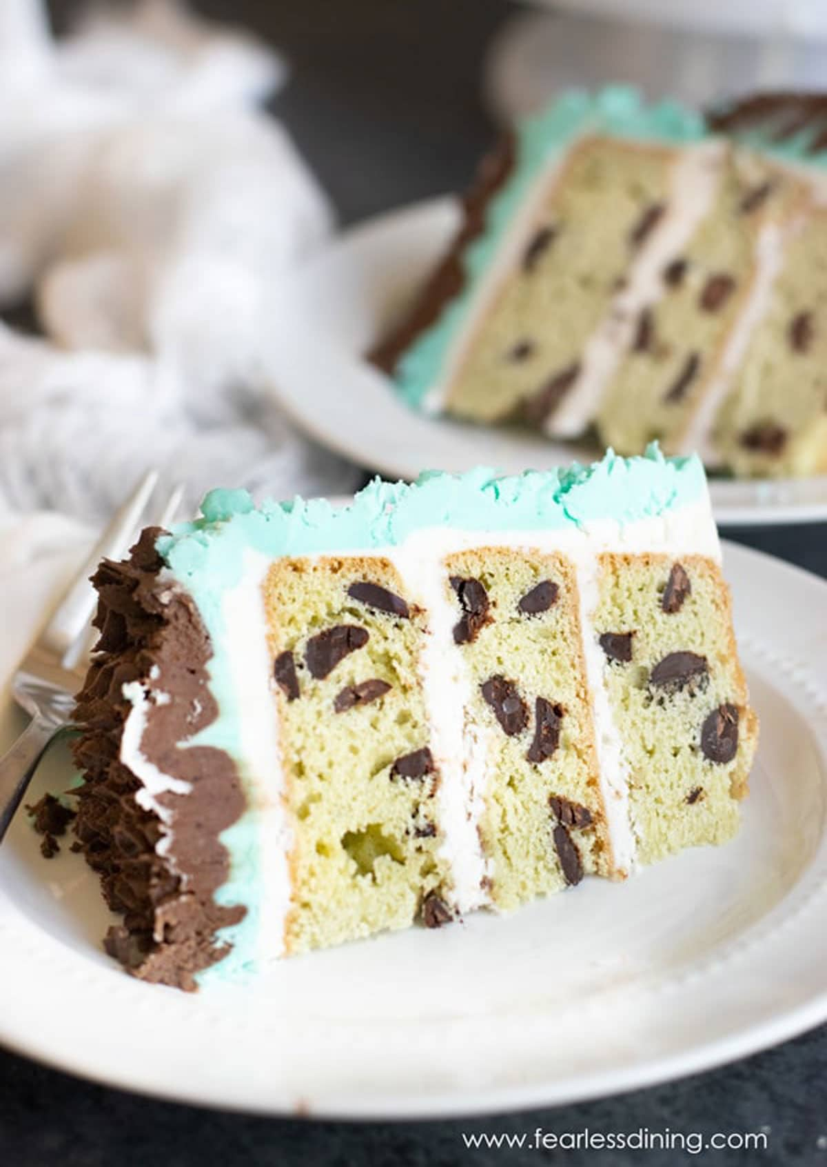 two slices of mint chocolate chip cake on small white plates