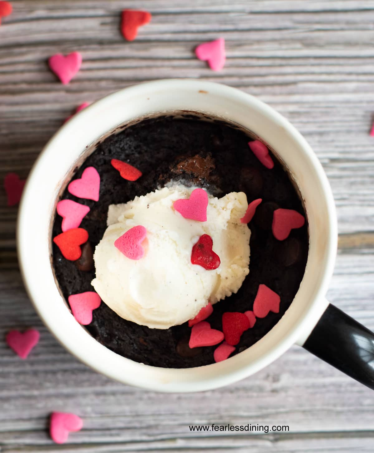 a cooked brownie mug with vanilla ice cream and pink and red heart sprinkles