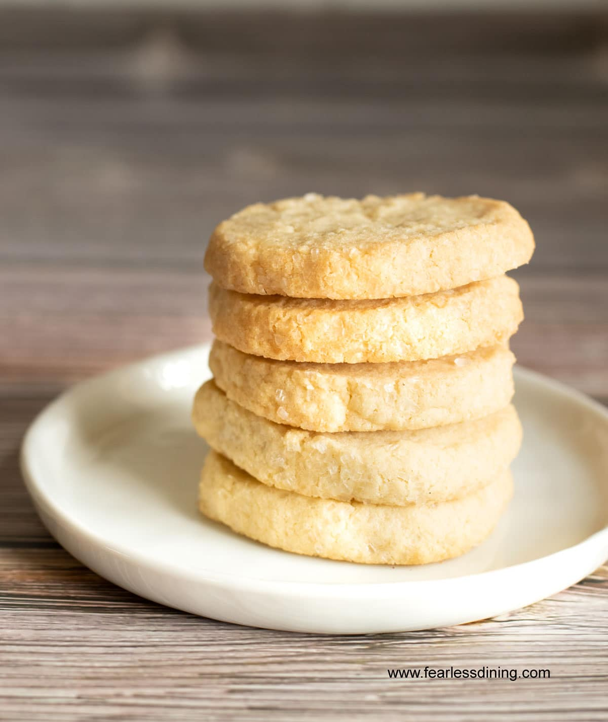 a stack of 5 gluten free sable cookies on a white plate