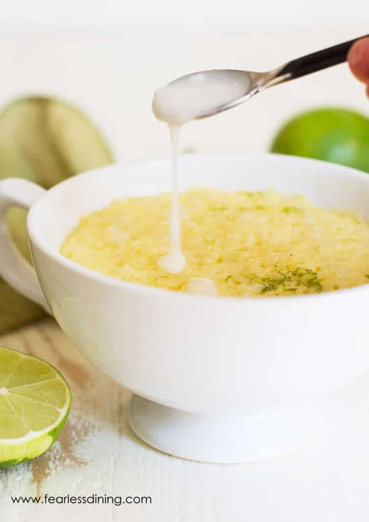 drizzling icing over a gluten free lime mug cake