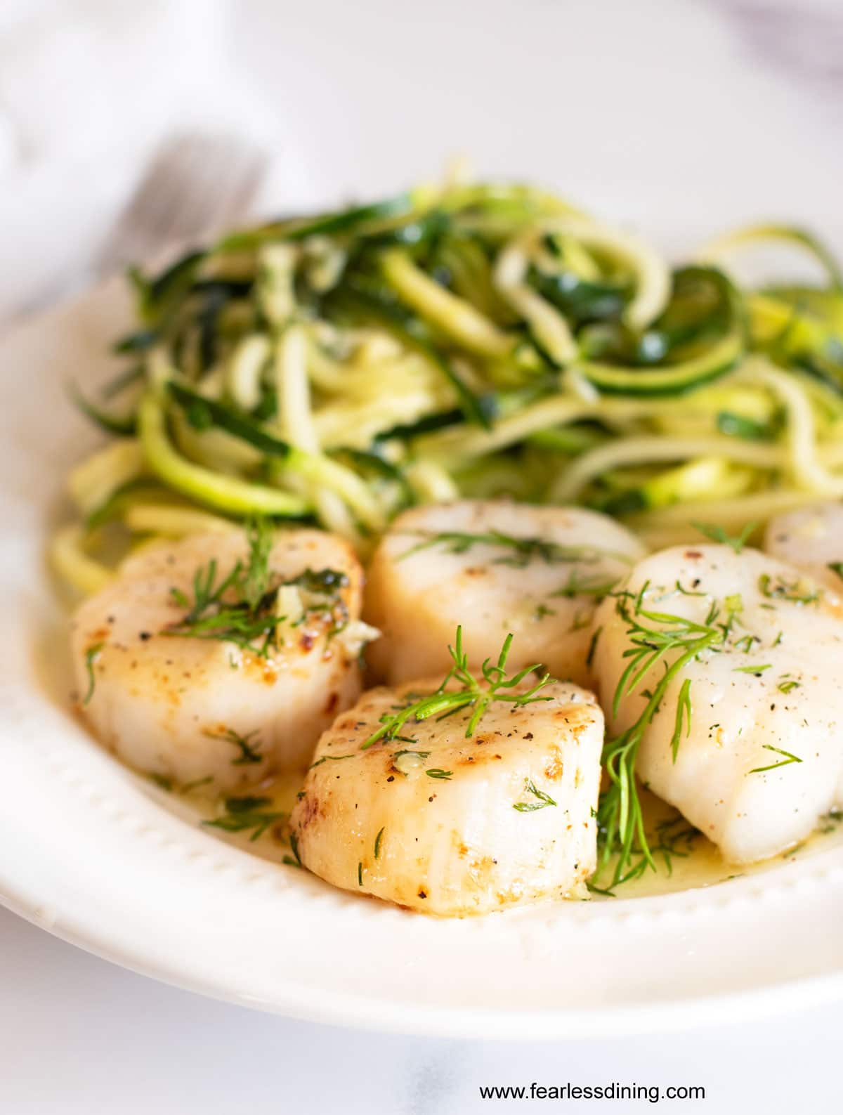 a plate of air fried scallops and zoodles with a garlic butter sauce