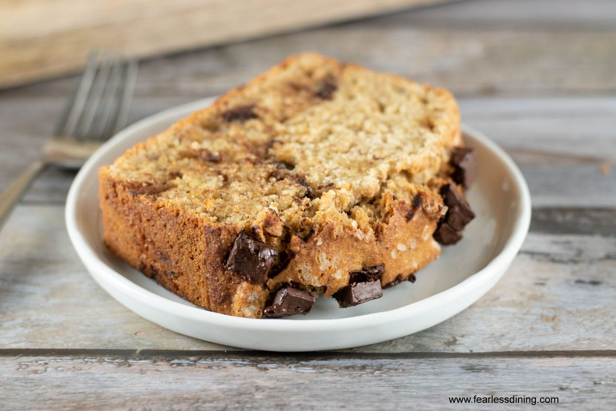 a slice of gluten free banana chocolate chunk bread on a white plate