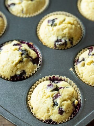 a muffin tin filled with baked gluten free blueberry muffins