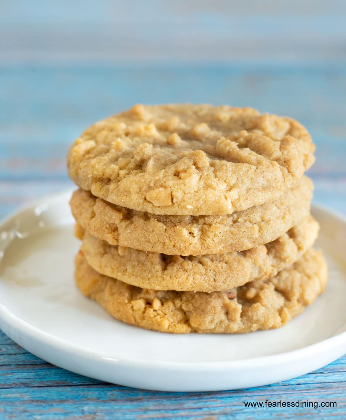 four peanut butter cookies on a white plate