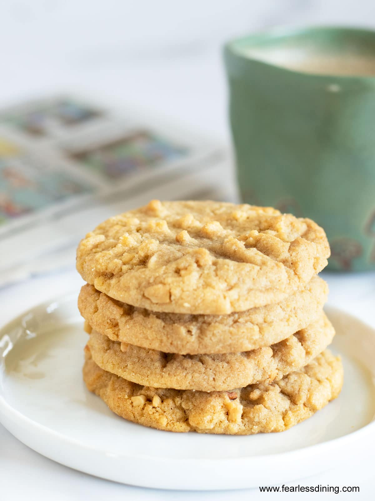 a stack of four peanut butter cookies next to a mug of coffee