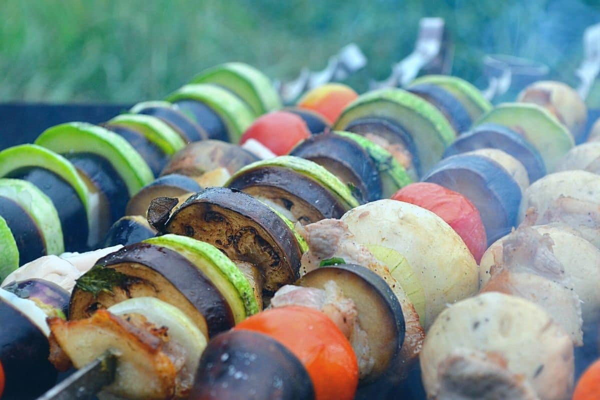 vegetables on skewers cooking on a grill