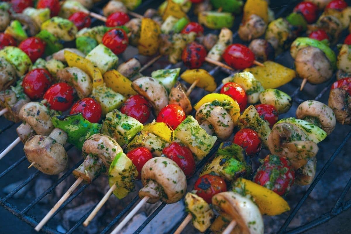 vegetables coated in pesto on skewers cooking on the grill