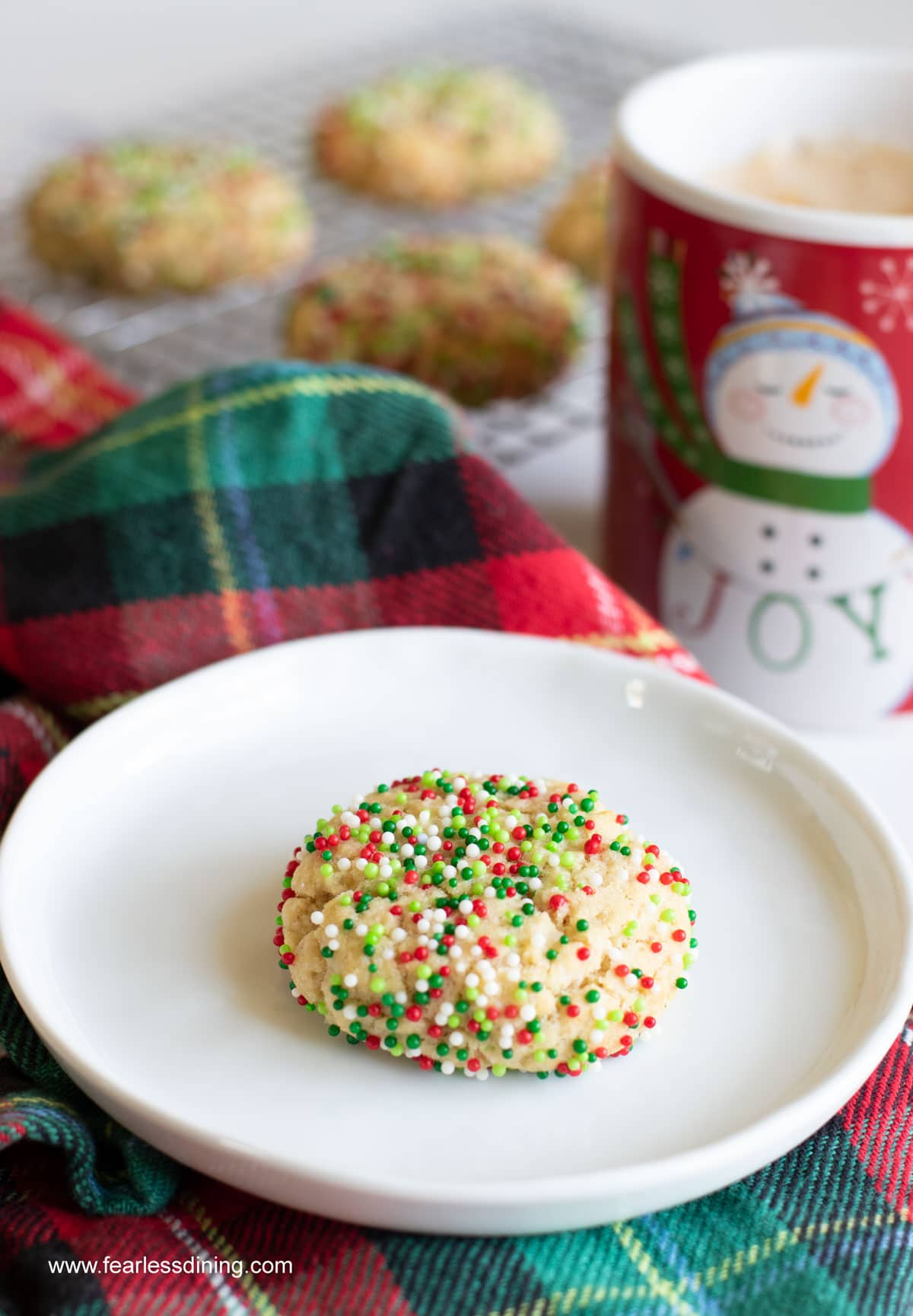 a gluten free cream cheese sugar cookie coated in red and green sprinkles on a plate