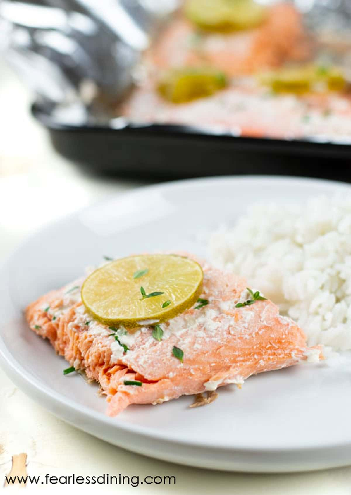 a slice of cooked salmon with rice on a white plate
