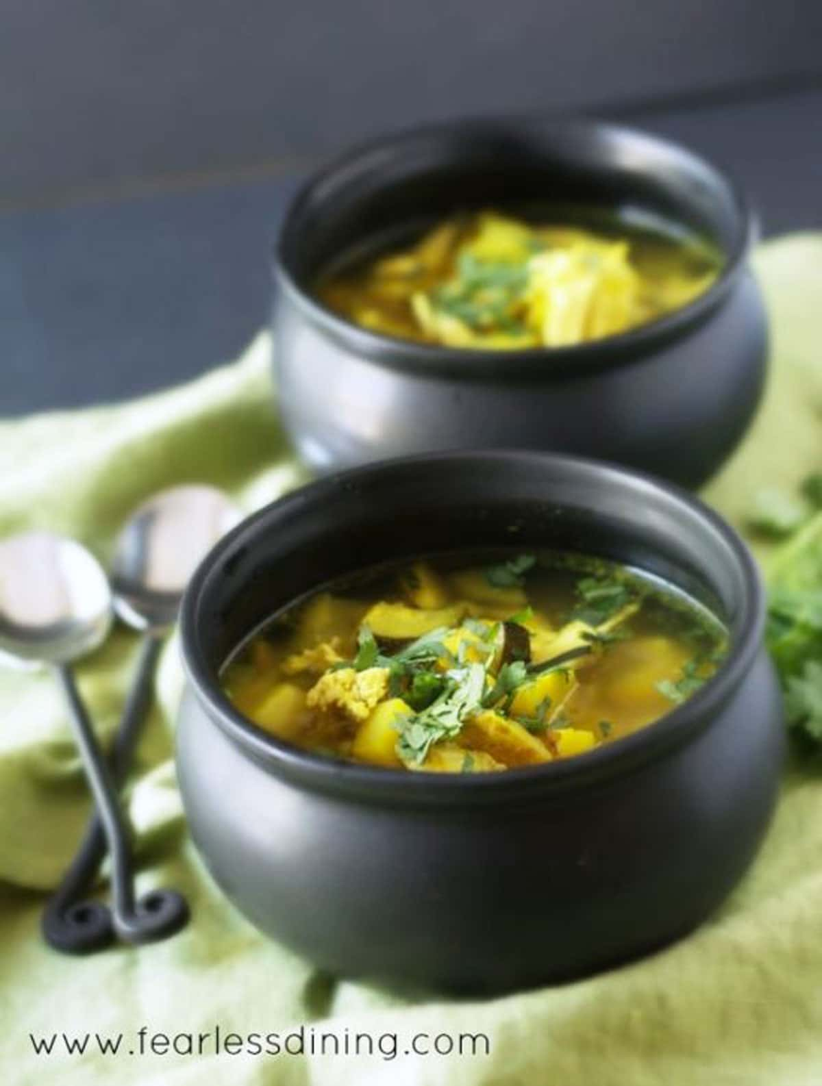 two black bowls filled with chicken turmeric soup