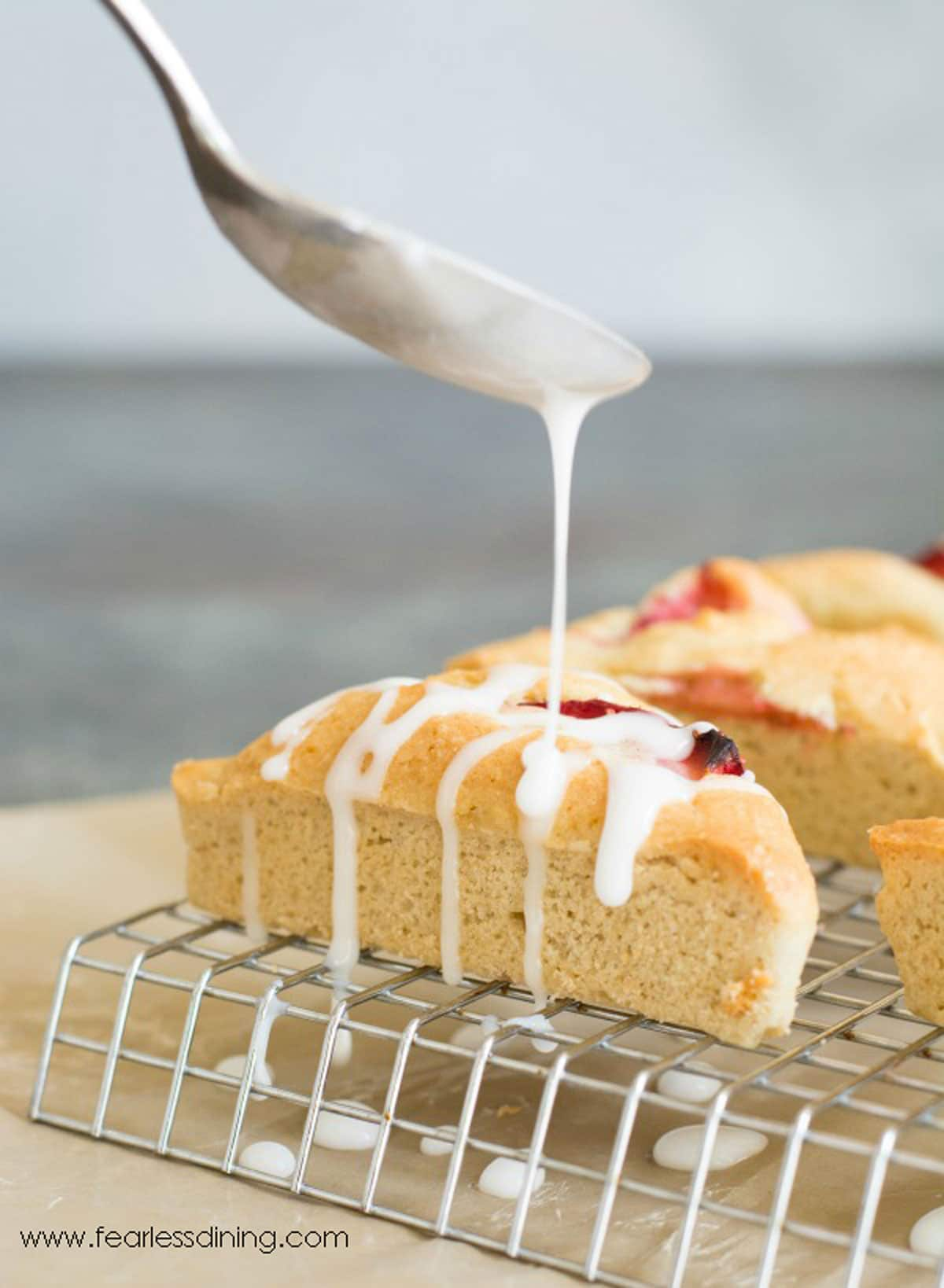 drizzling icing over strawberry scones