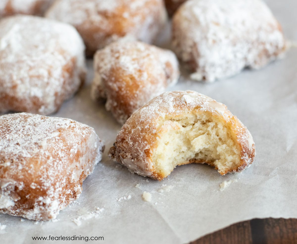 gluten free beignets on parchment paper. One has a bite taken out.