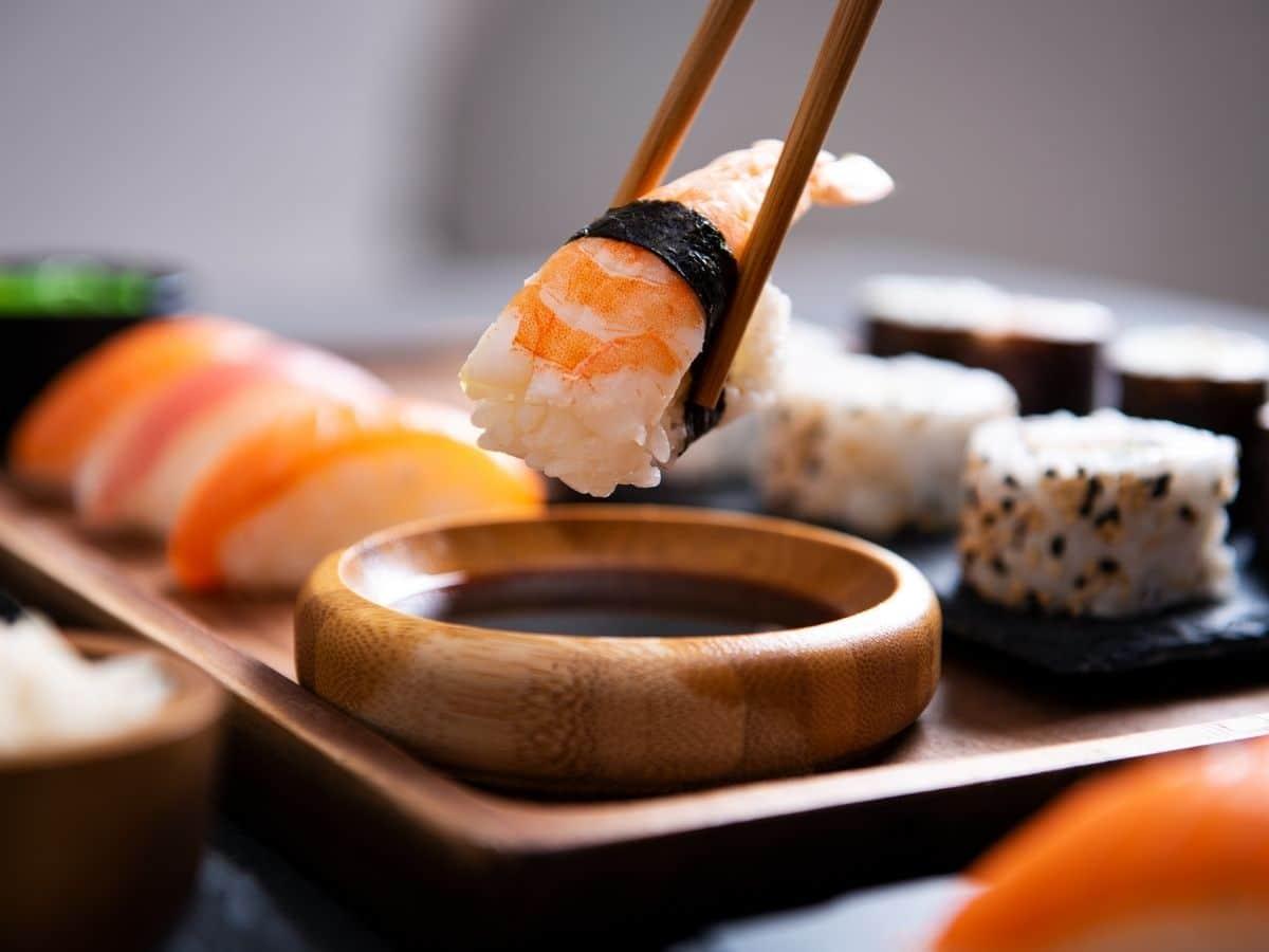 dipping a piece of shrimp sushi into tamari