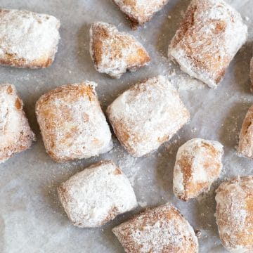 the top view of a bunch of powdered sugar coated beignets