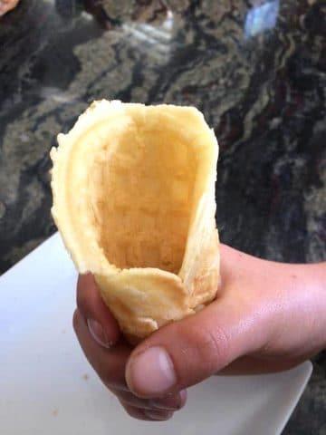 a hand holding a diy gluten free waffle cone
