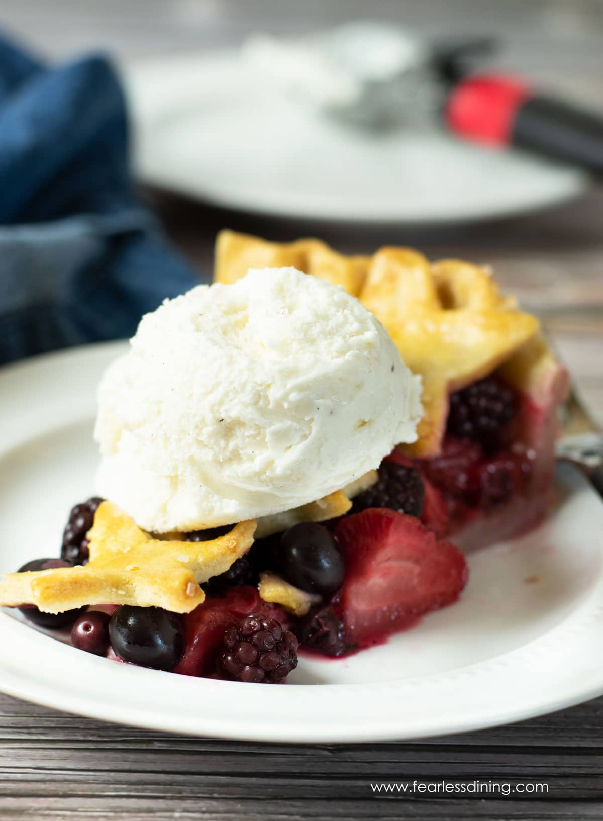 a slice of mixed berry pie with a scoop of ice cream on top