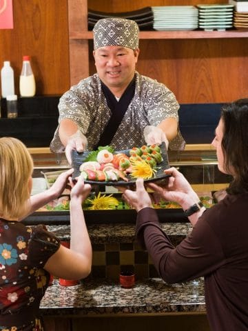 a couple being served in a sushi restaurant