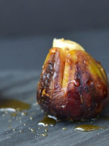 a single brown grilled fig stuffed with brie