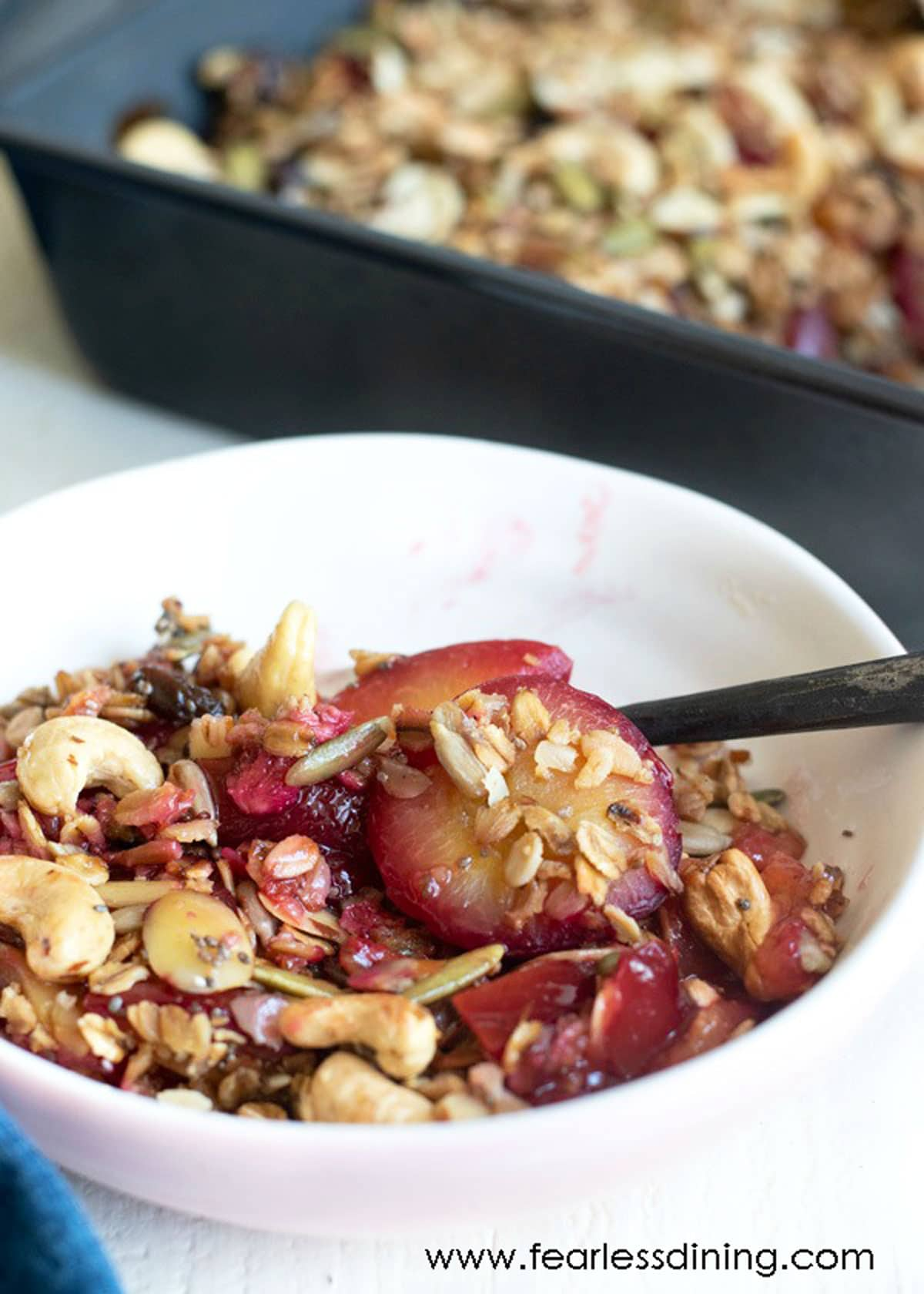 a white bowl filled with plum crisp