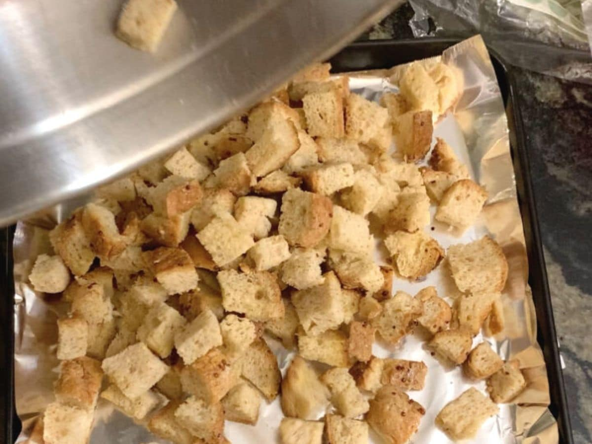 pouring croutons onto a baking sheet