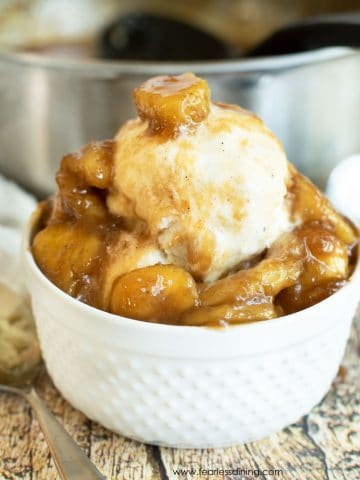a white bowl filled with ice cream and caramelized bananas
