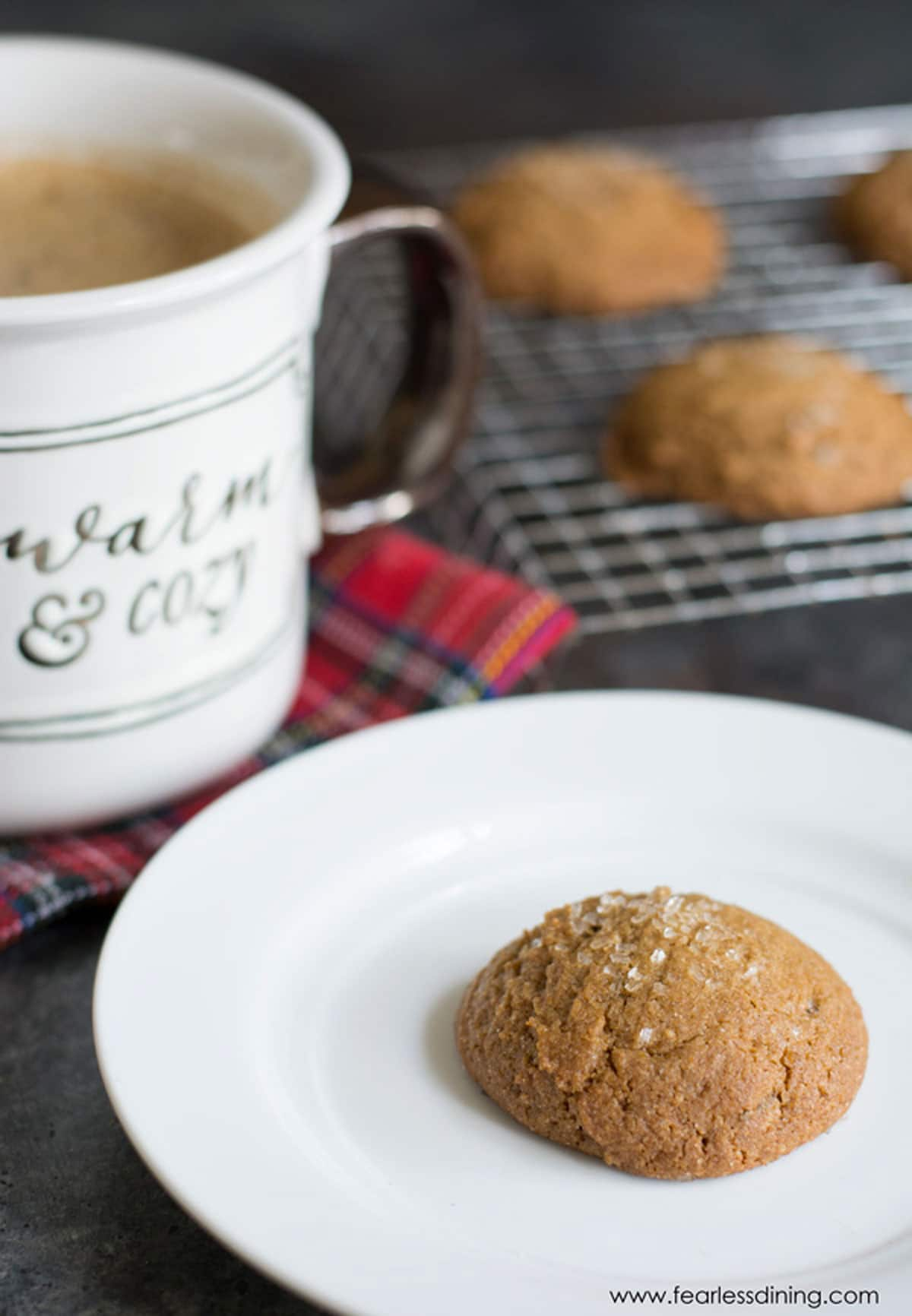 a ginger cookie on a plate next to a mug of coffee