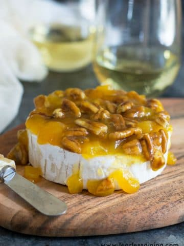 a brie wheel topped with a mango pecan sauce