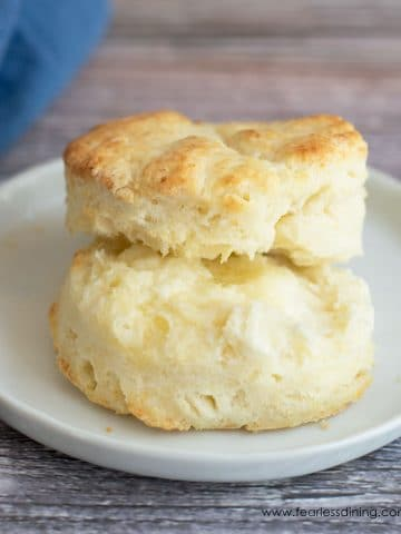a biscuit cut in half on a plate with butter