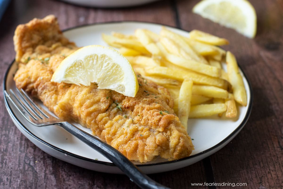 an air fried catfish filet on a plate with french fries