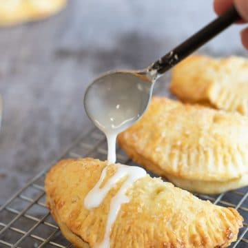 Drizzling icing over a gluten free air fried hand pie