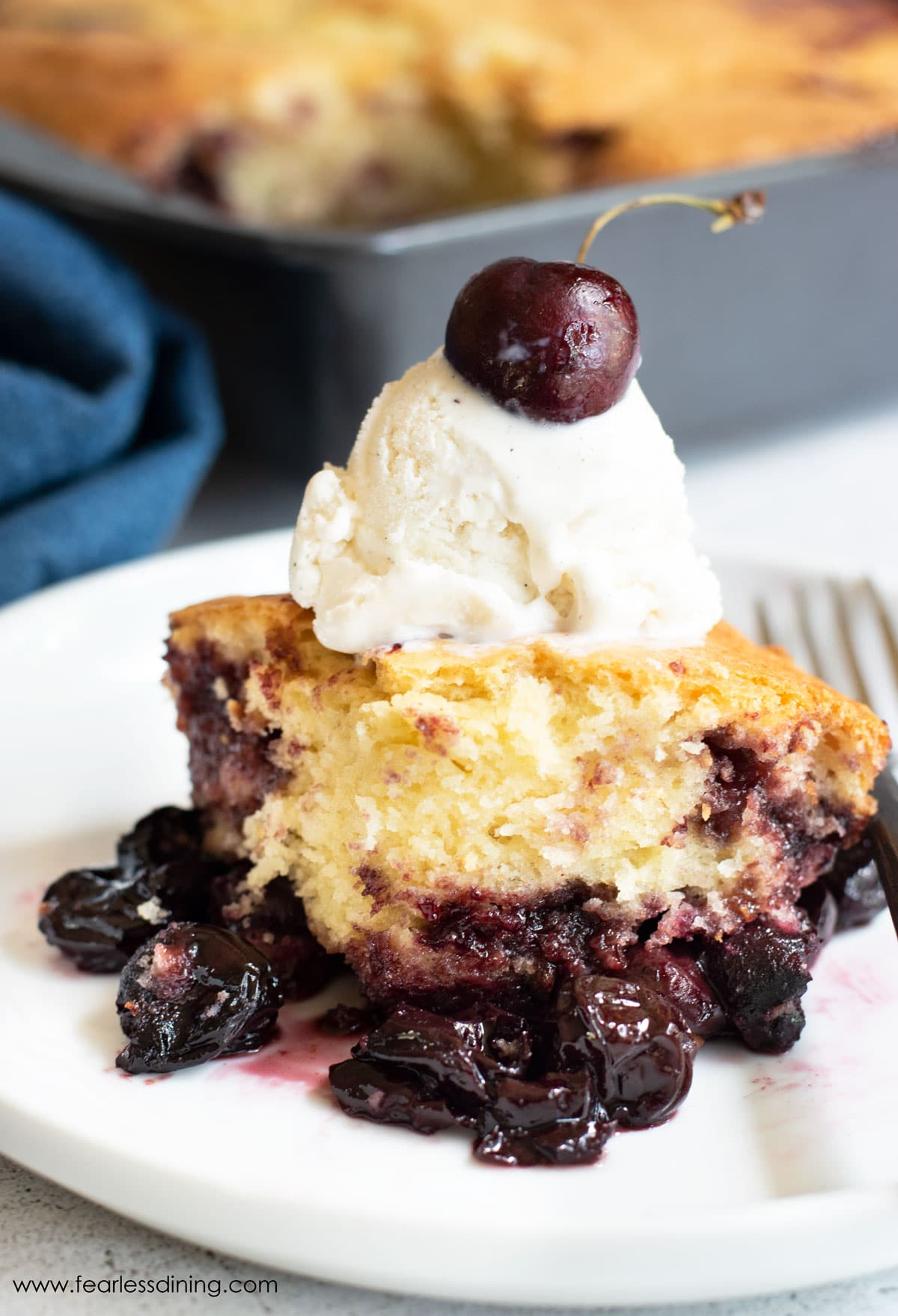 a serving of gluten free cake mix cherry cobbler topped with vanilla ice cream