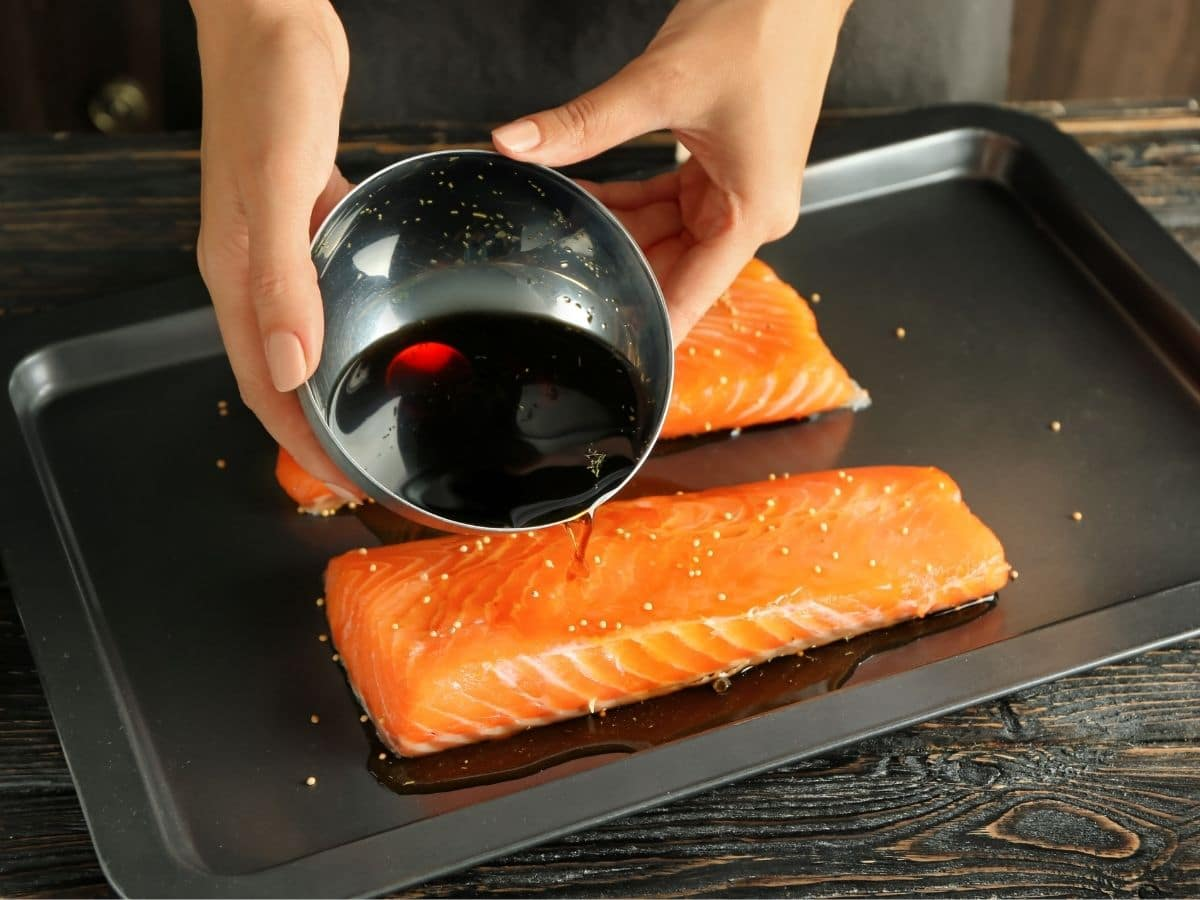 pouring marinade over raw salmon