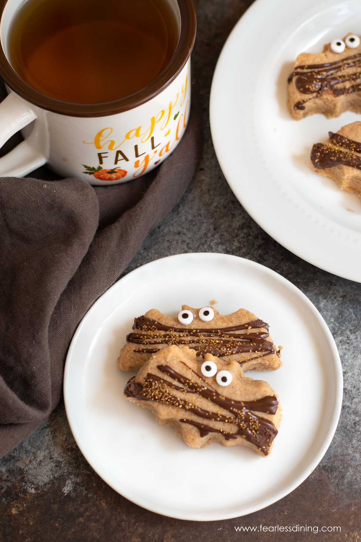 the top view of two bat shaped pumpkin spice shortbread cookies on a plate