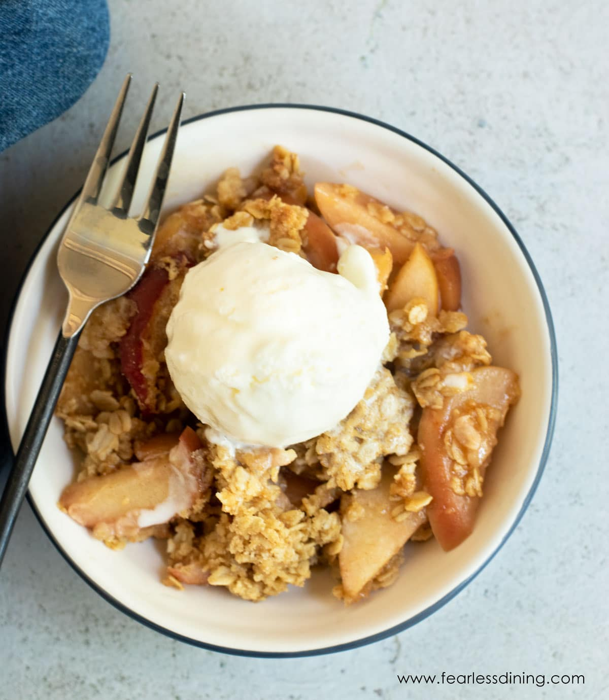 the top view of a bowl of gluten free apple crisp with ice cream