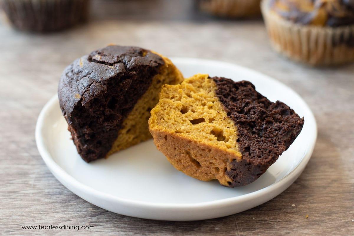 a chocolate pumpkin muffin cut in half on a plate