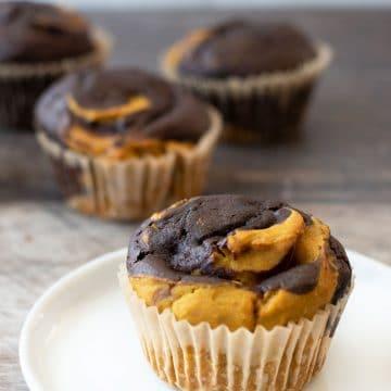 a pumpkin chocolate swirl muffin on a plate