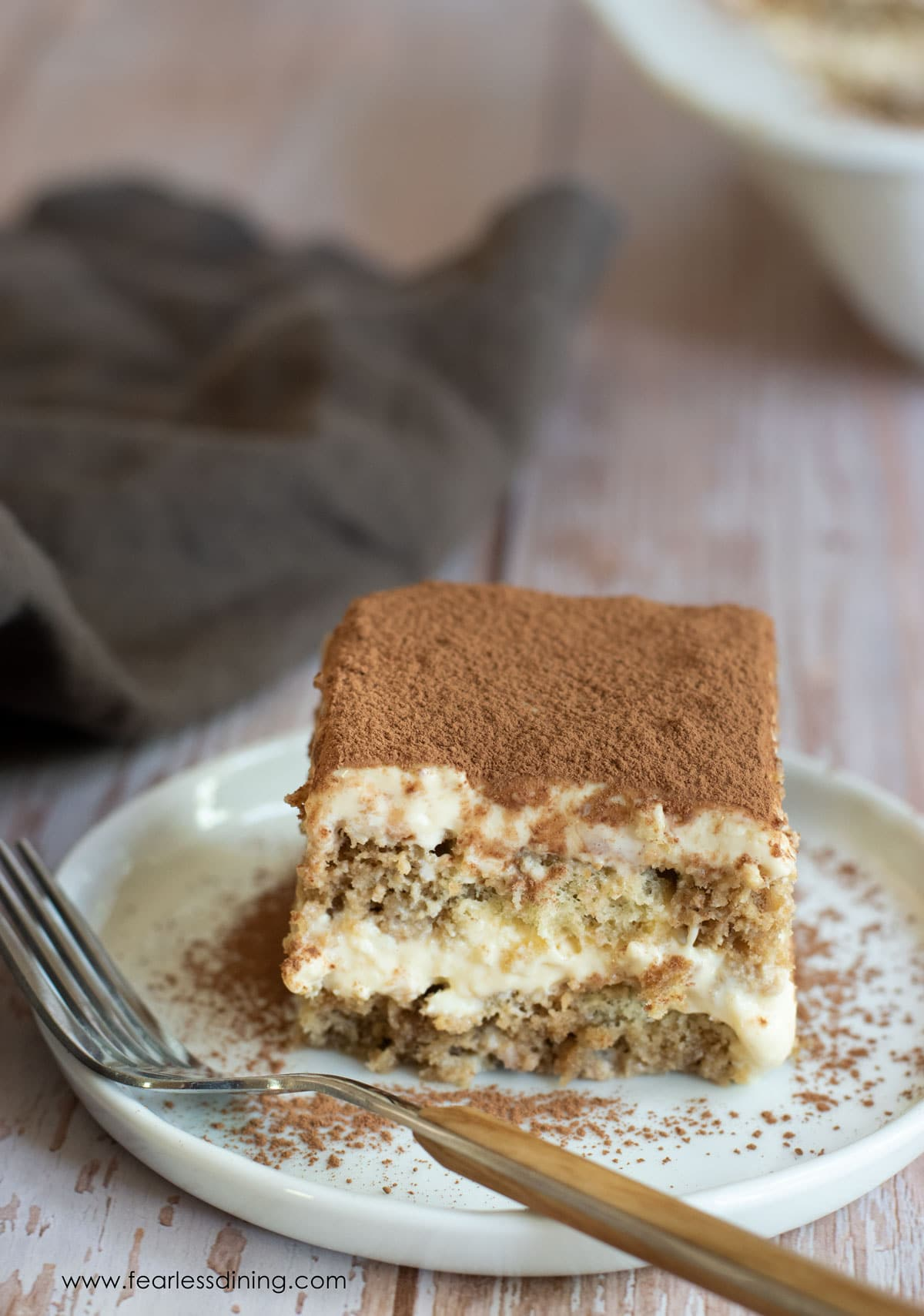 a piece of tiramisu on a plate with a brown fork