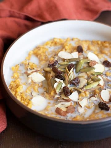 a bowl of pumpkin steel cut oats topped with nuts and raisins