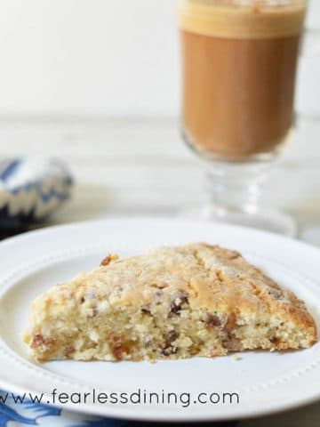 a gluten free date scone on a plate with a latte behind the plate