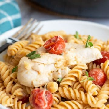 a plate of chicken pasta with feta and tomatoes