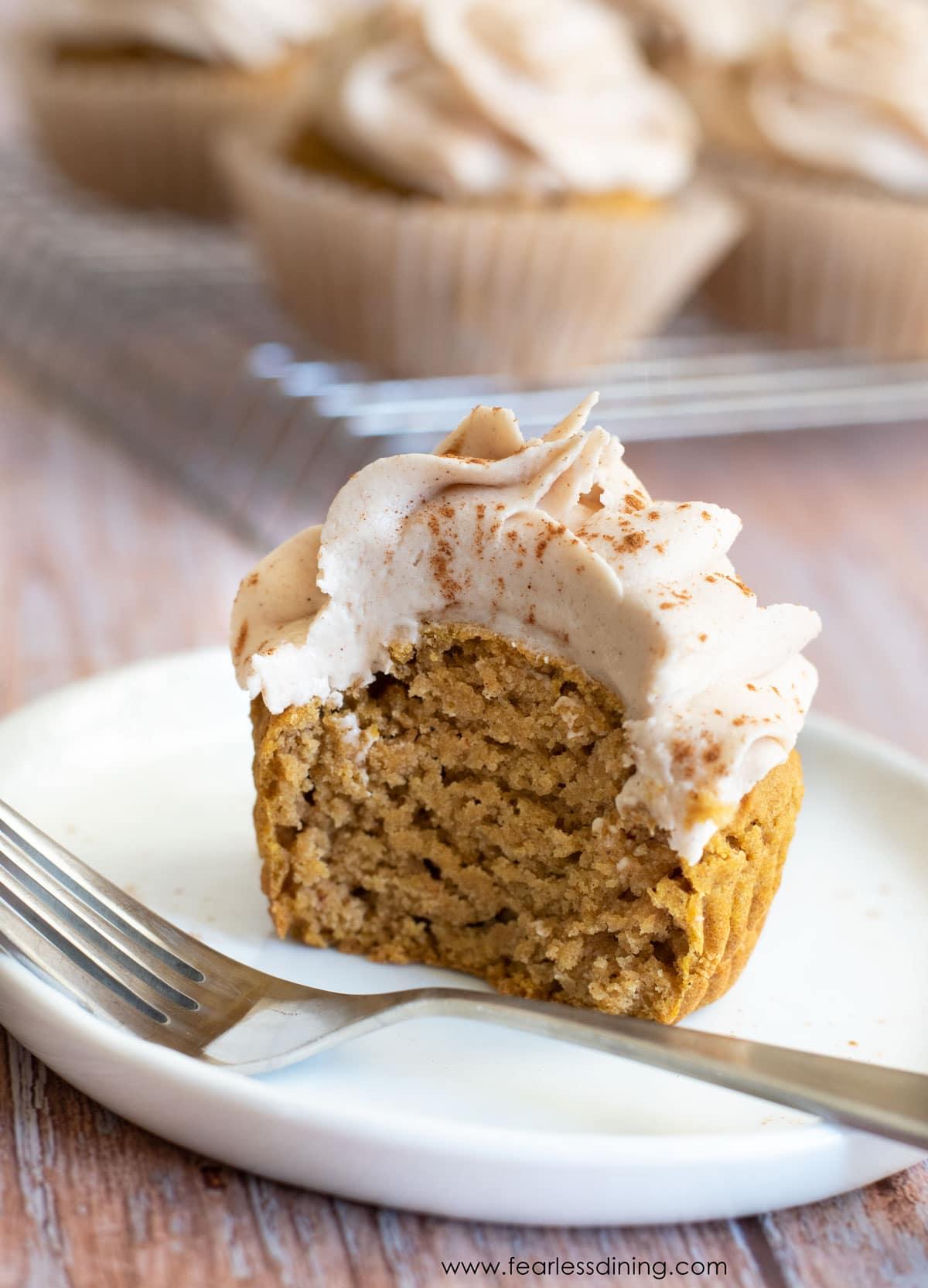 half of a pumpkin cupcake on a white plate